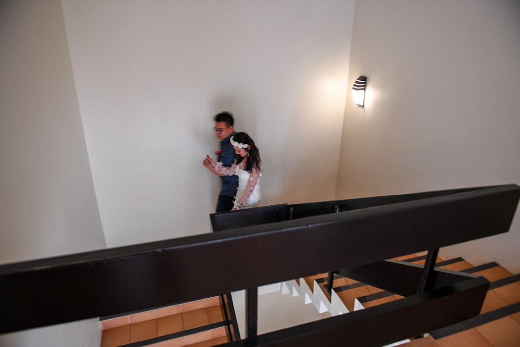 Long shot of asian husband and bride walk down stairs