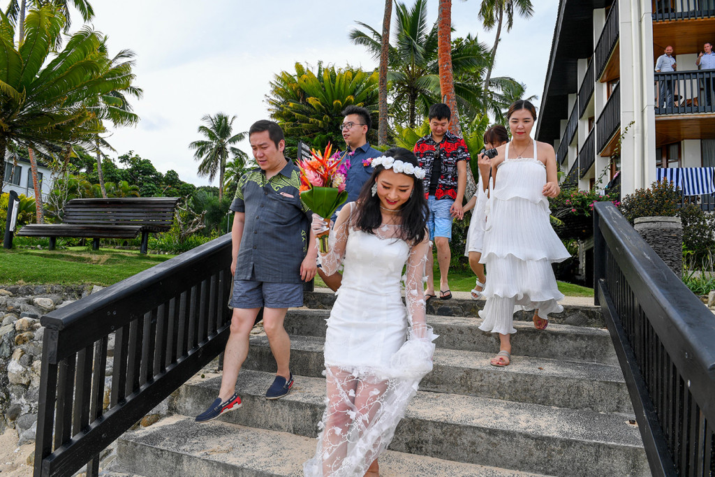 Stunning asian bride and groom walk down stairs to their 5 star wedding in Warwick Fiji