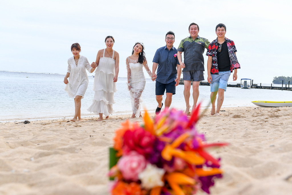 Married couple and wedding guests walk on beach with orange and pink bouquet soft in the foreground