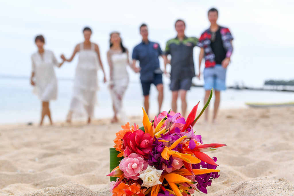 Married couple and wedding guests walk on beach with orange and pink bouquet sharp in the foreground