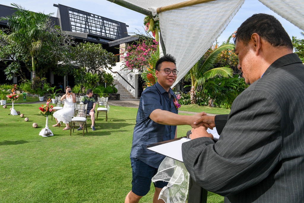 Asian groom greets celebrant at the altar