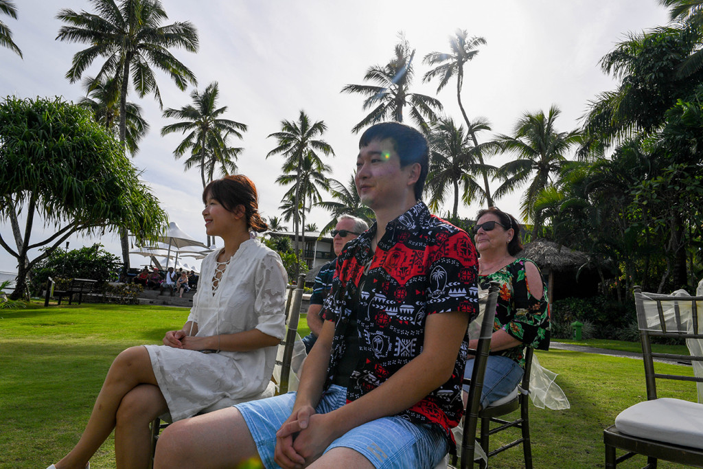 Wedding guests sit and watch against palm trees in Warwick Fiji