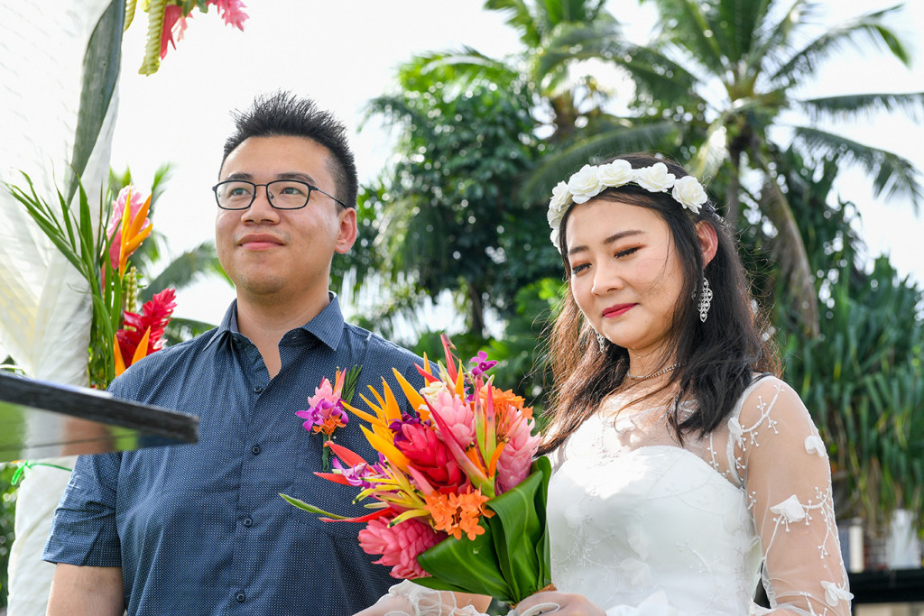 Asian couple exchange vows at the altar in Warwick beach wedding