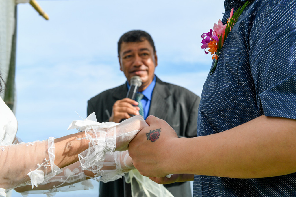Closeup of couple holding hands while Fiji celebrant officiates wedding in Fiji Warwick