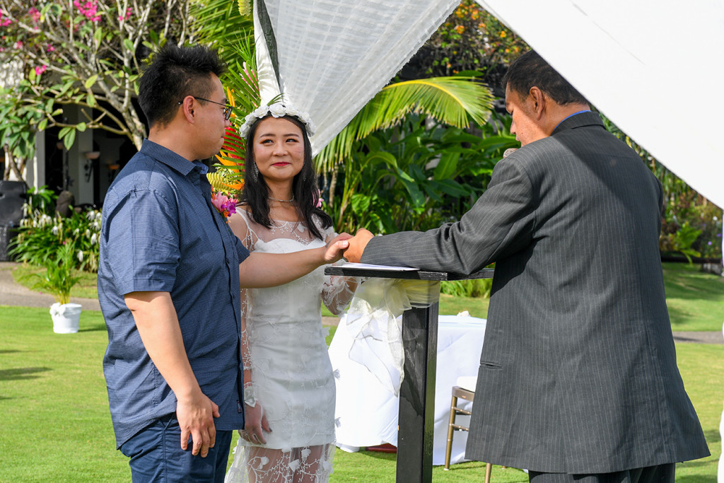 Asian groom places hand on the bible while exchanging vows in Fiji Warwick