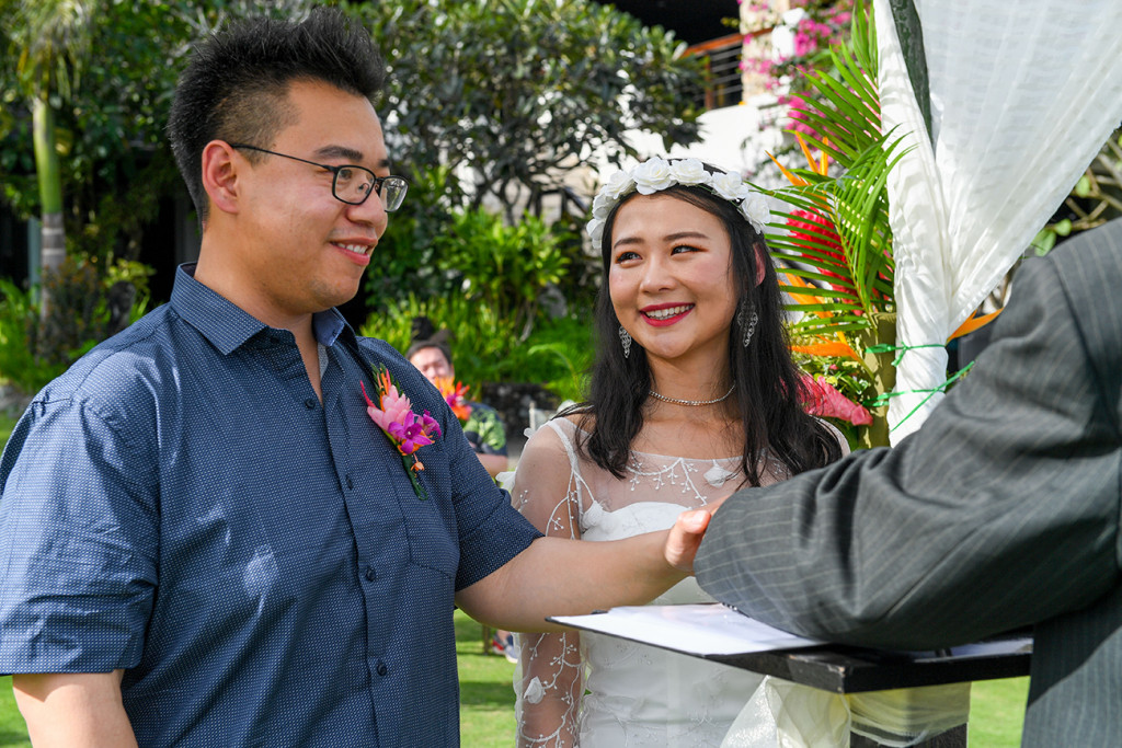 Closeup of Asian groom places hand on the bible while exchanging vows in Fiji Warwick