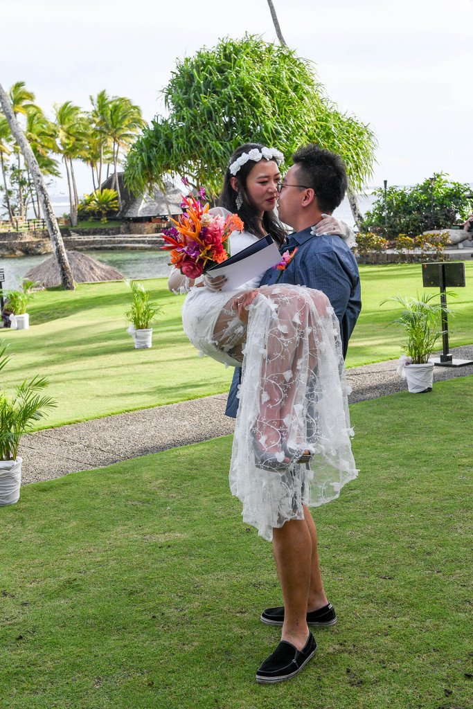 Groom carries and kisses his bride in Warwick Fiji