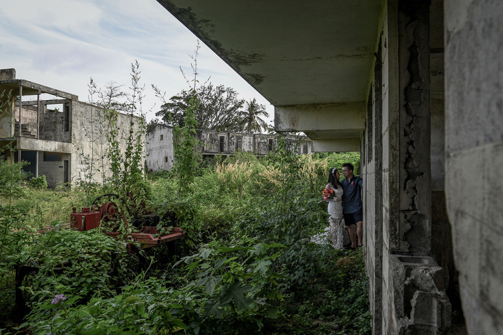 Married couple against abandoned building and overgrow grass in Warwick Fiji photoshoot