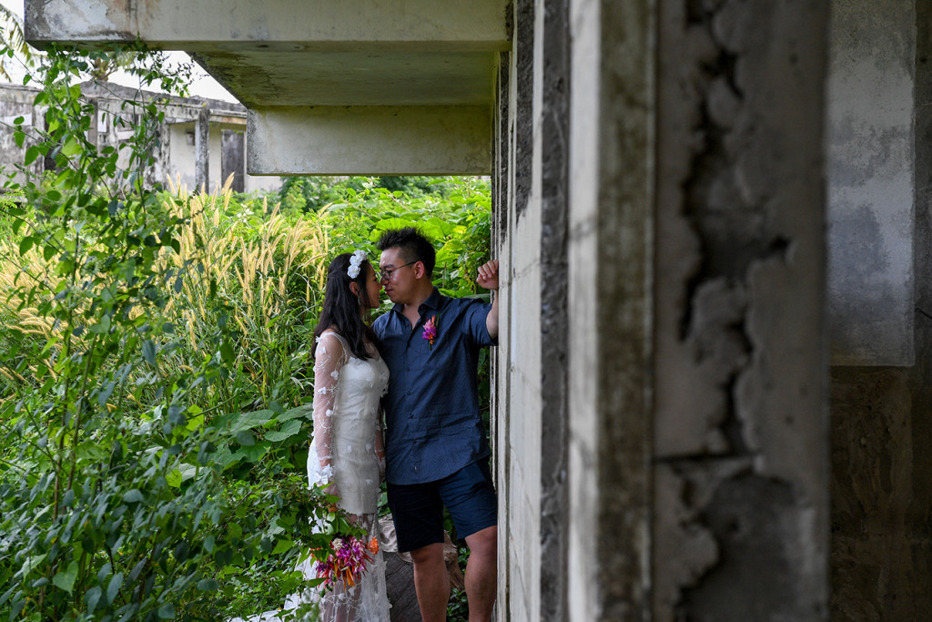 Married asian couple kiss against abandoned building and overgrown background