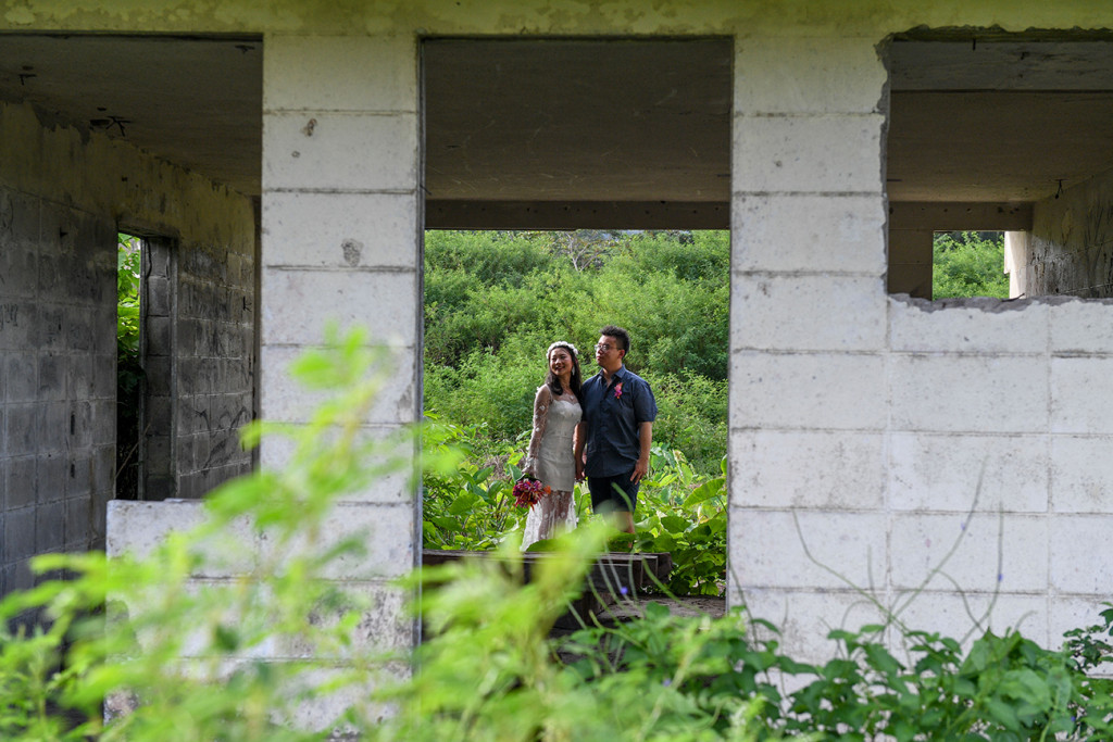 Married Asian couple standing behind abandoned building in Warwick Fiji photoshoot