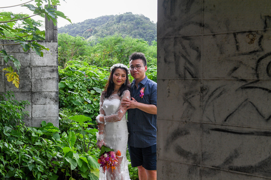Married asian couple pose for wedding photoshoot behind abandoned building