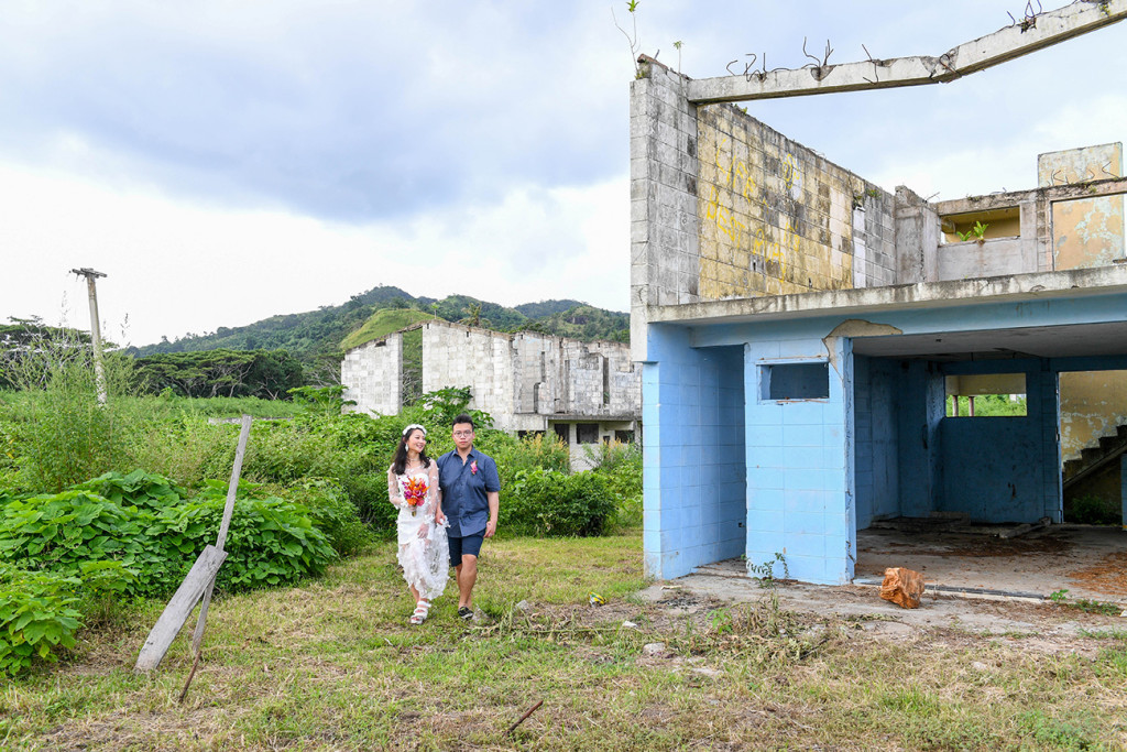 Wide shot of newly married couple standing against abandoned building in Warwick Fiji
