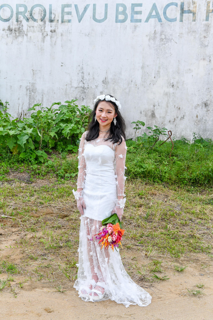 Stunning asian bride poses with her bouquet agains abandoned building in Warwick Fiji