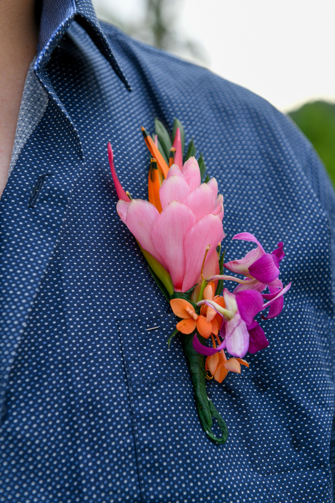 Closeup of groom's pink and orange Fiji floral boutonniere