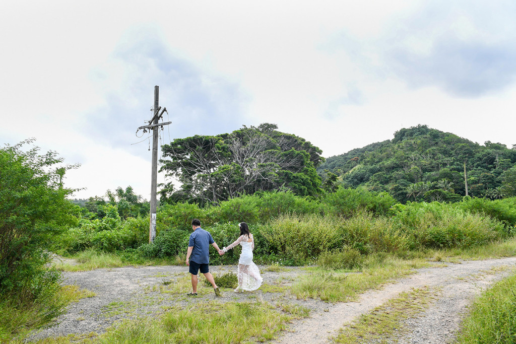 Bride and groom walk into the sunset in wide shot greenery Fiji