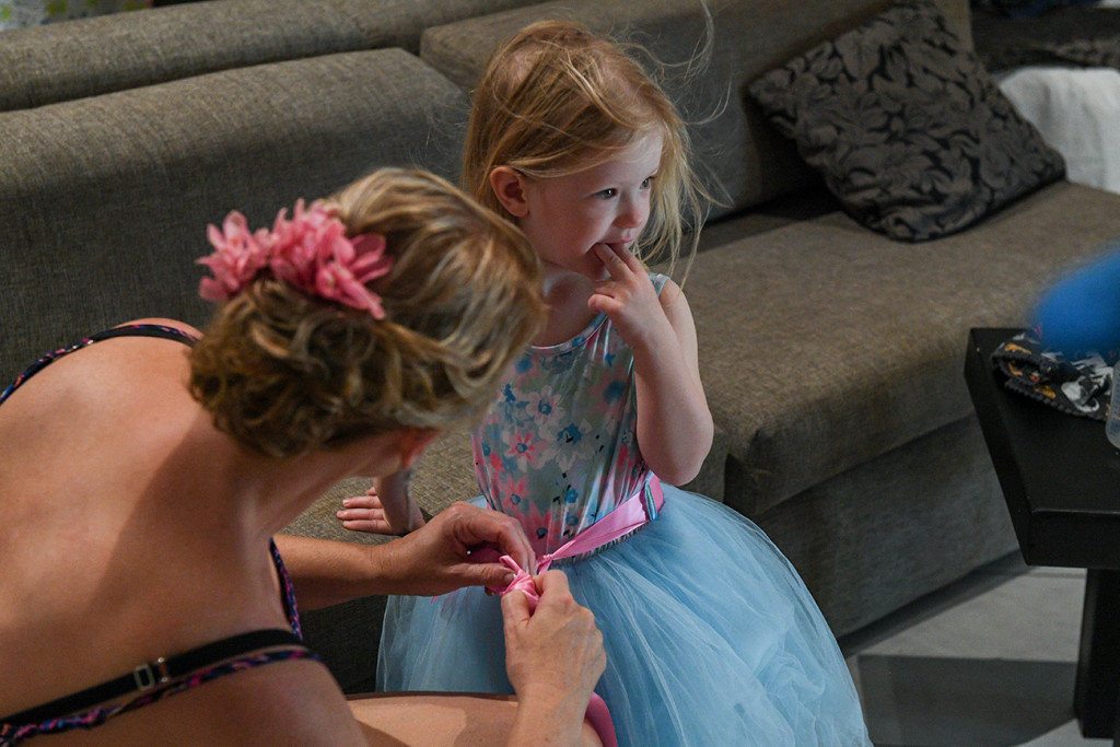 Bride helps flowergirl tie dress in Fiji wedding