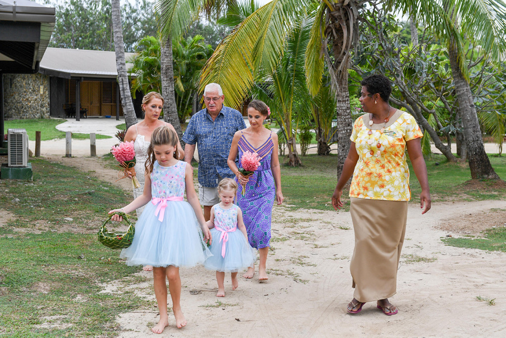 Flower girls walking down sandy beach in Plantation Island Resort