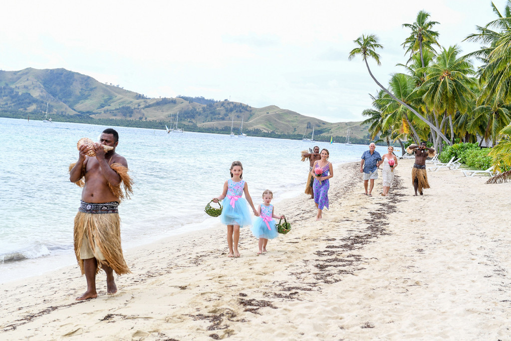 Flower girls and bride walk along the sea on beach at Plantation Island Resort Fiji wedding