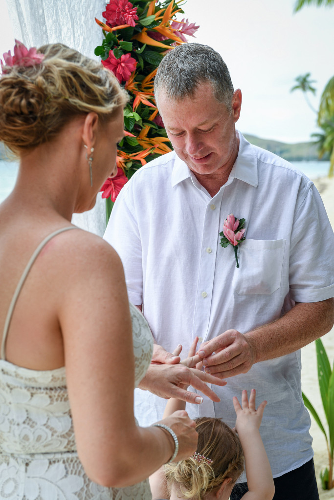 Groom puts ring on his bride in beach wedding Plantation Island Resort Fiji