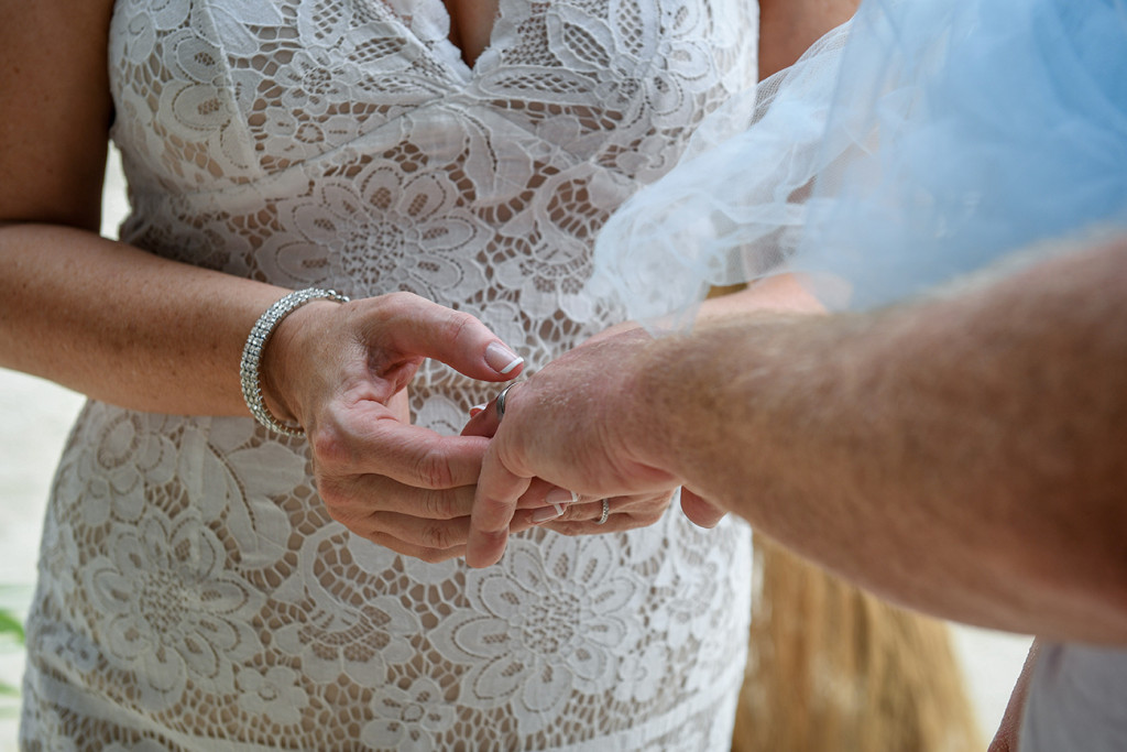 Closeup of bride putting ring on groom in Fiji wedding