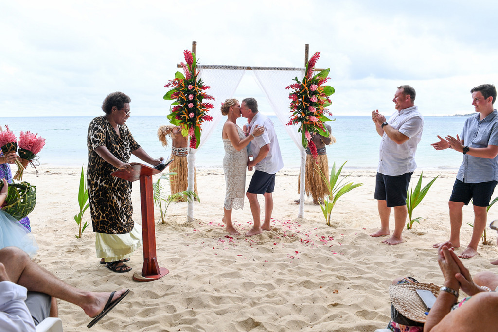 Bride and groom kiss on the beach against the sea in Tropical beach wedding Fiji
