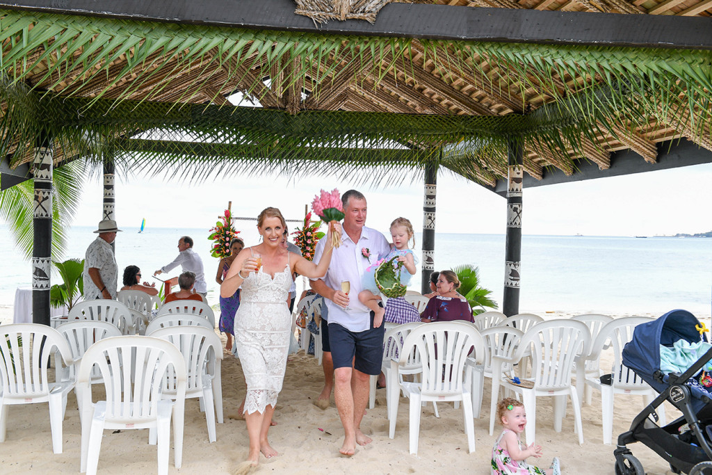 Happily married couple walk down aisle of beach Plantations Island Resort Wedding
