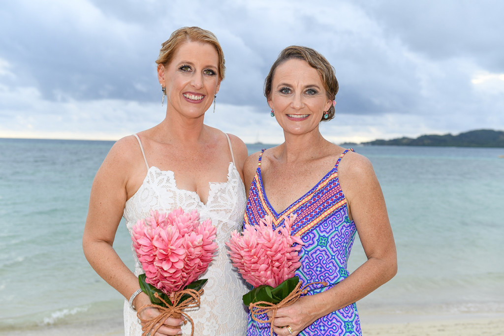 Bride and bridesmaid in bohemian dress and tropical flower bouquet at Plantation Island Resort Fiji