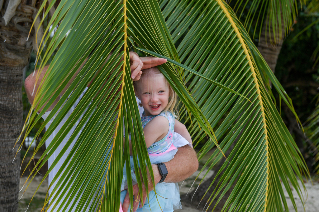 Happy flower girl hiding in the palm trees in Fiji Island Resort