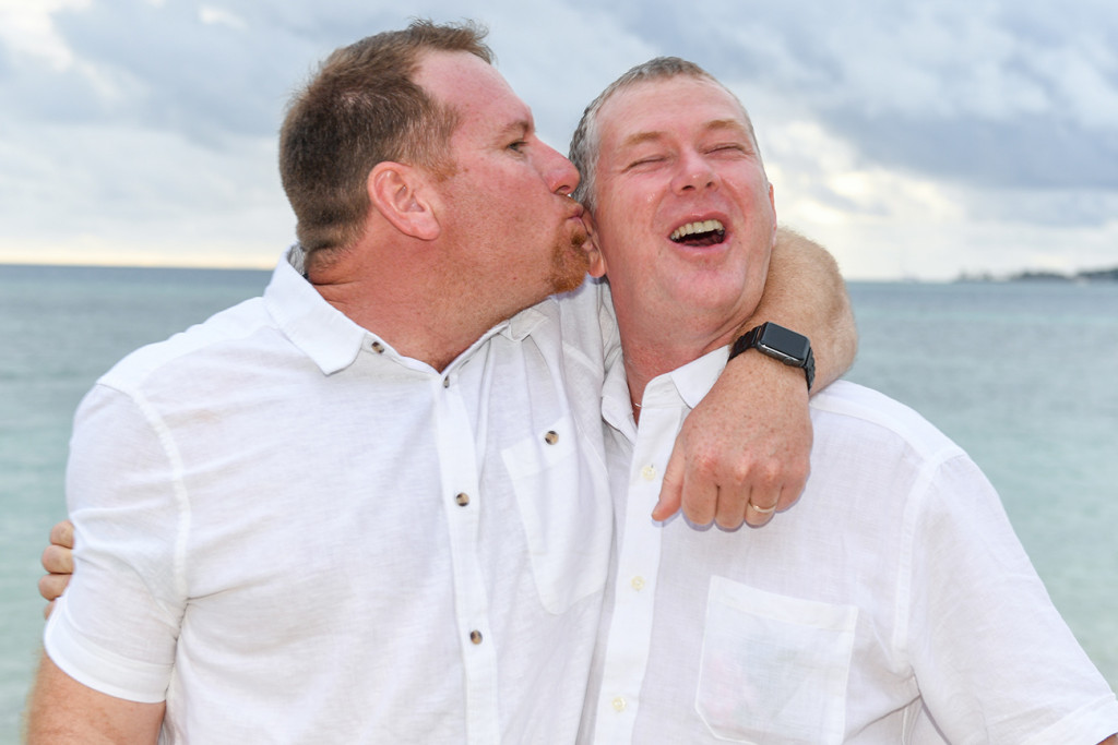Brother kisses groom against sea