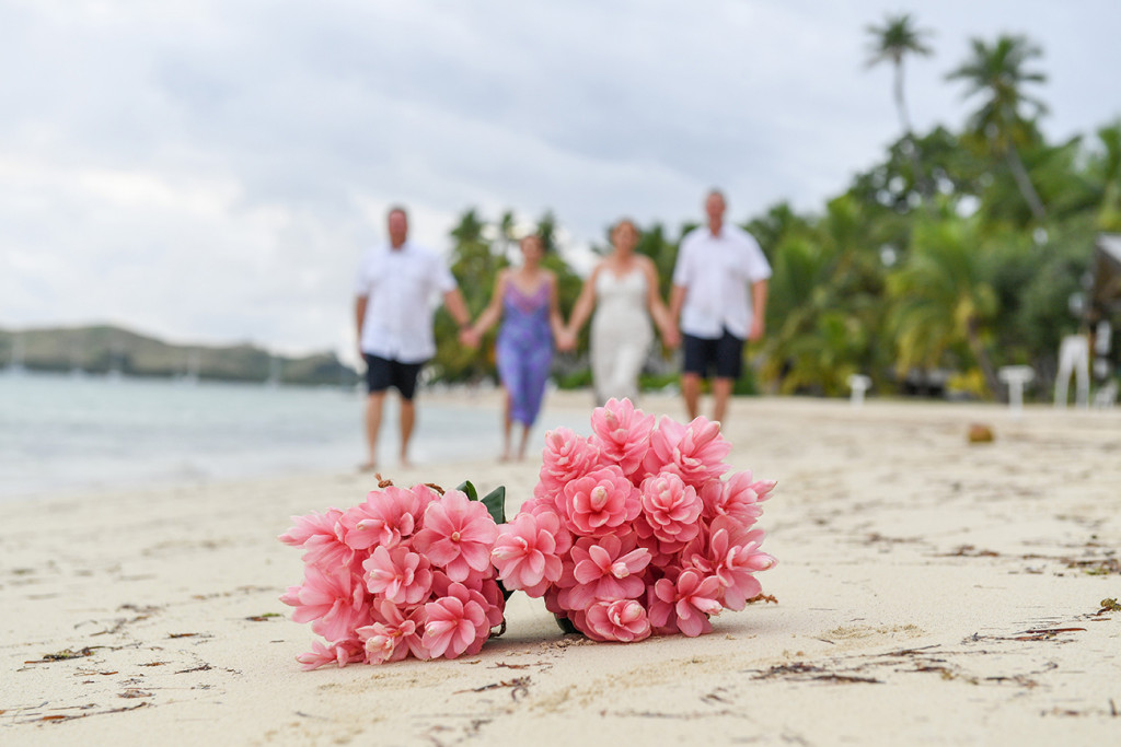 Bouquet of tropical flowers in the foreground and family in background at Fiji tropical wedding background blurred