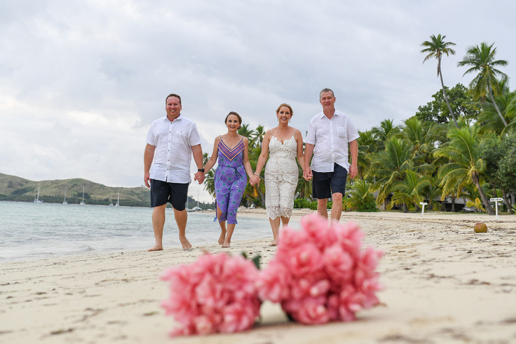 Blurred Bouquet of tropical flowers in the foreground and family in background at Fiji tropical wedding