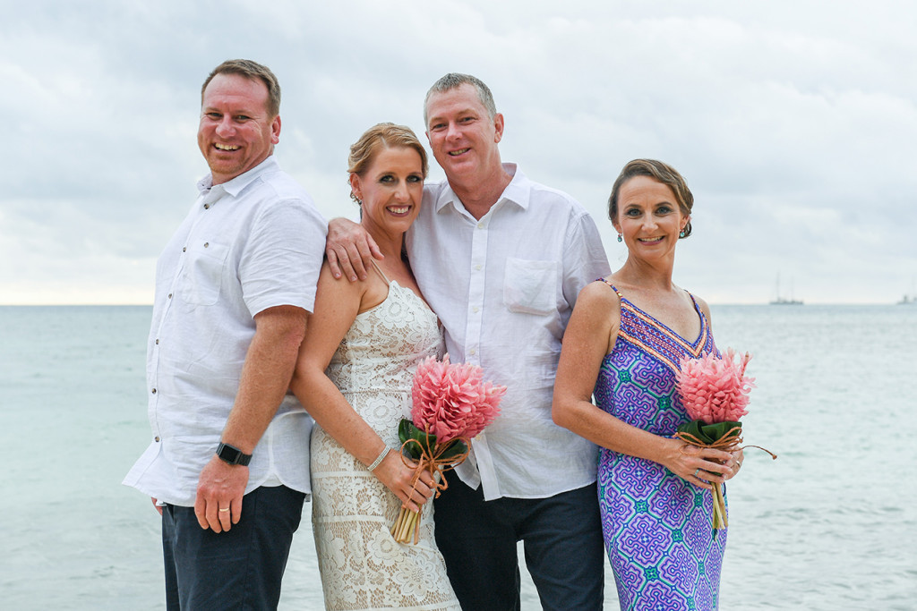 Newly married couple pose with couple of honour against sea in Plantain Island Resort Fiji