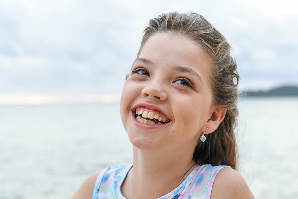 closeup of flowergirl laughing against sea