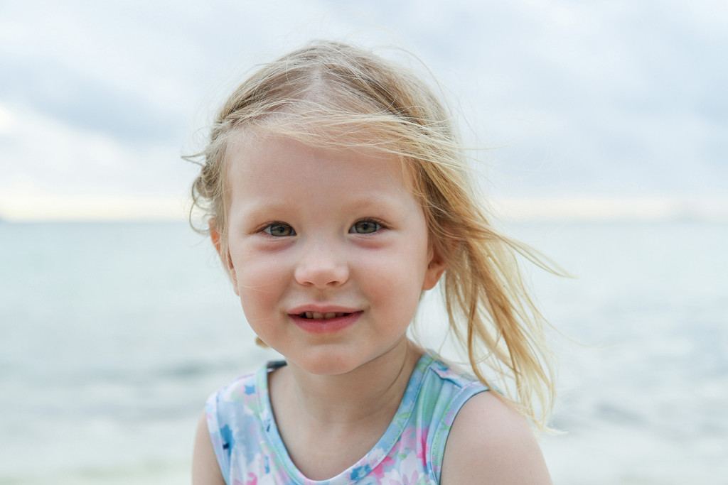 Cute blonde baby girl smiles against the sea