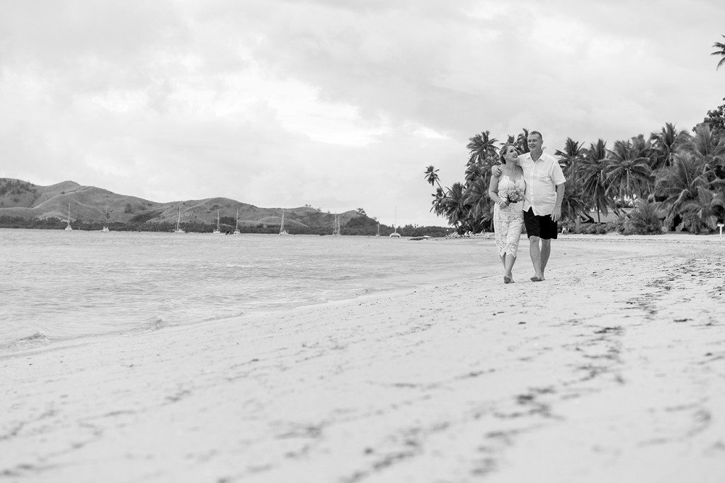 Black and white photo of Bride and groom strolling on beach during Plantation Island Resort Wedding