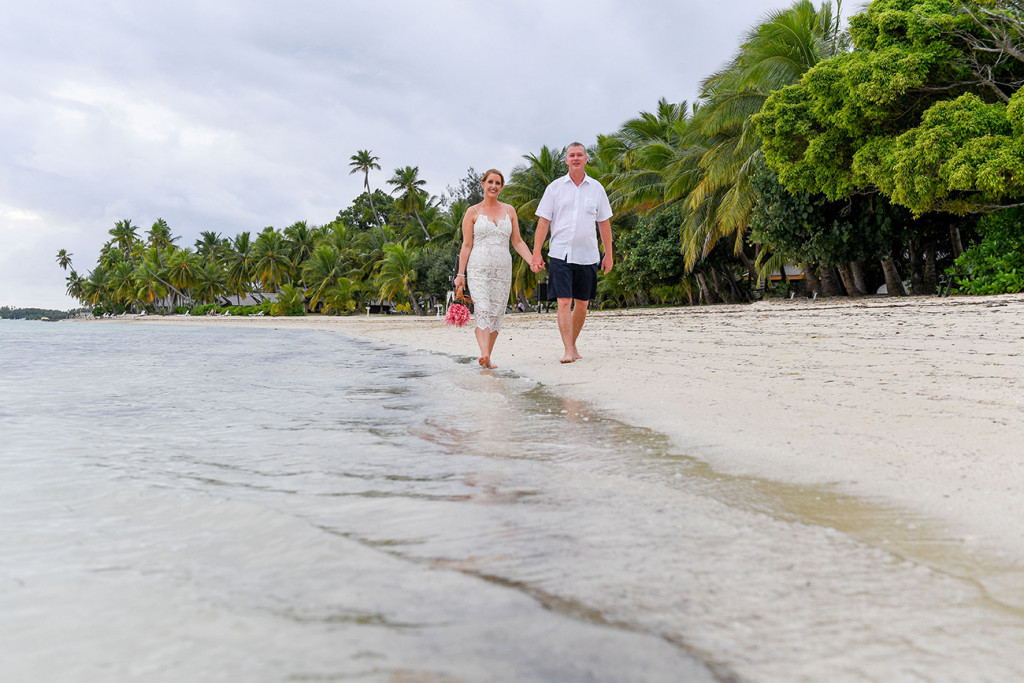 Bride and groom stroll by the sea in Plantation Island Resort Fiji
