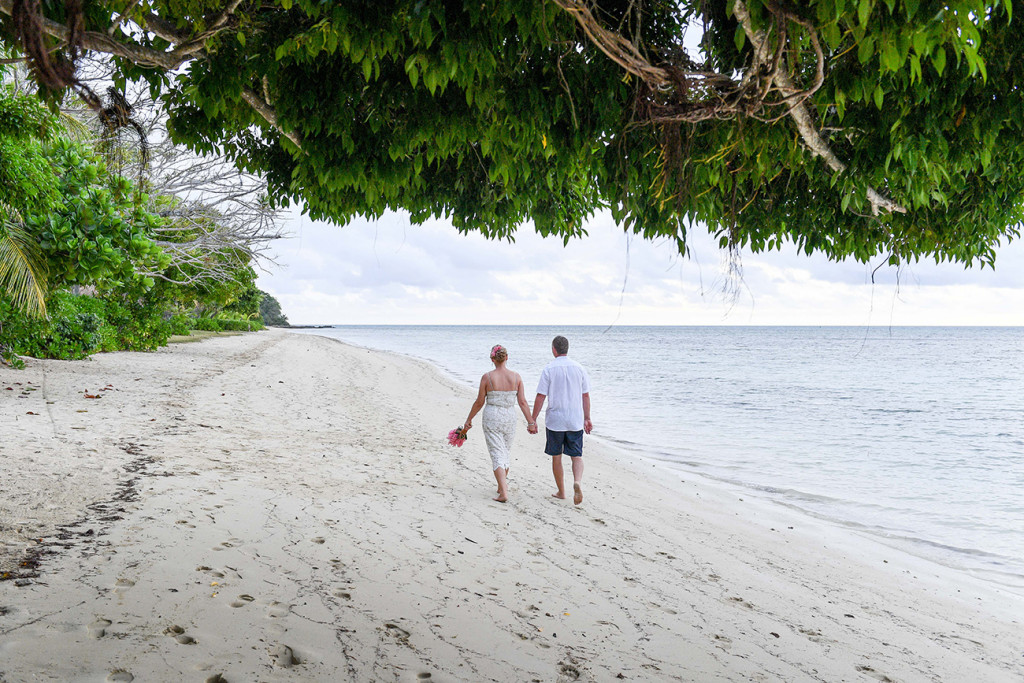Back shot of bride and groom strolling on Fiji island beach