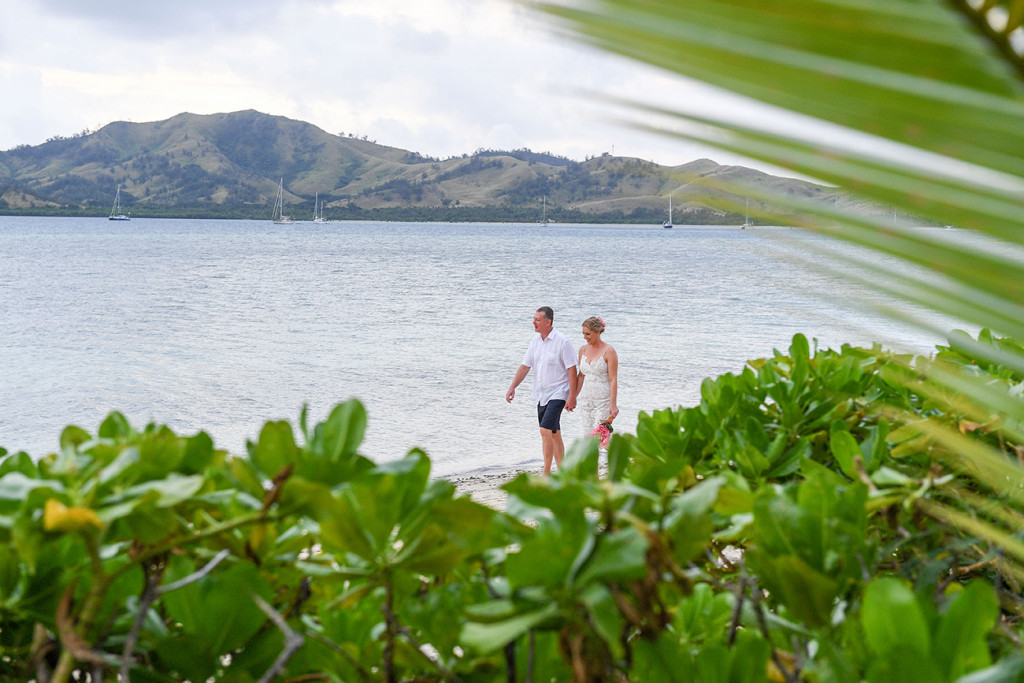 Long shot through palm trees of Bride and groom strolling against Fiji sea