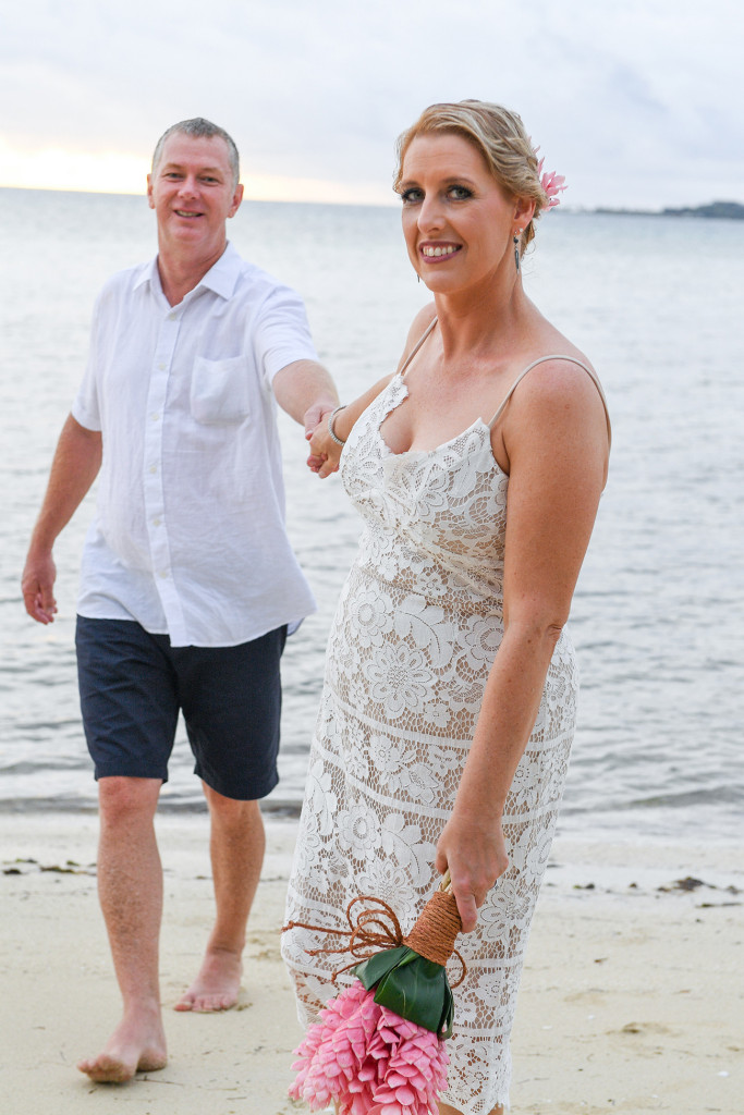 Bride holds onto groom against the Fiji sea