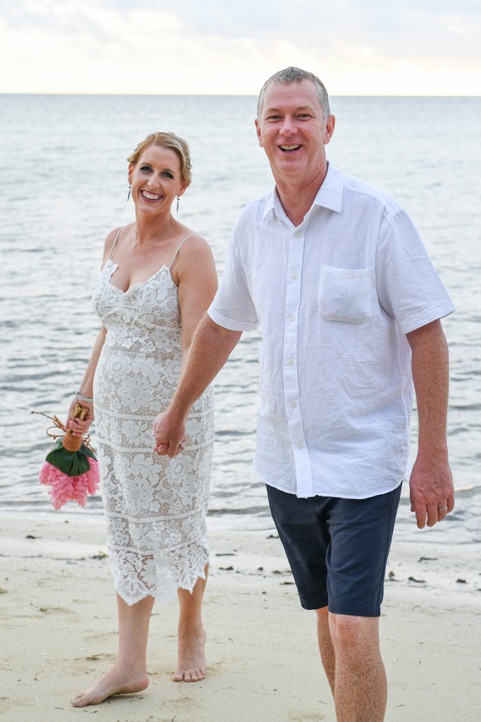Bride and groom laugh while holding hands against sea