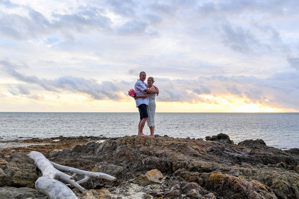 Wide landscape shot of Bride and groom standing on coral rocks against fiery sunset
