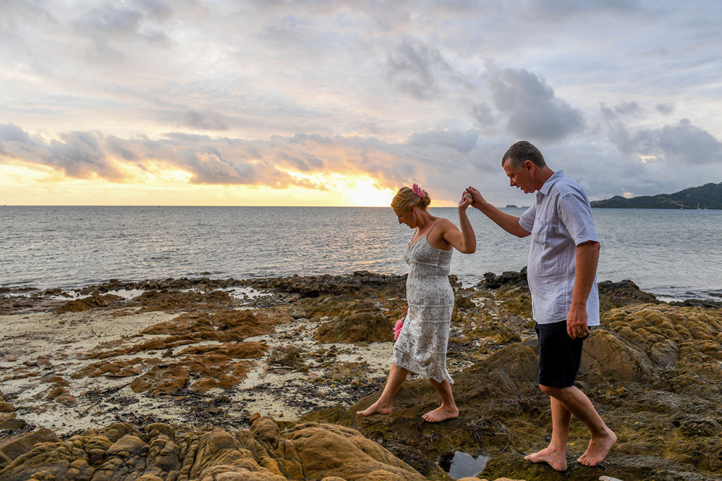 Groom helps bride walk on rocks by the sea