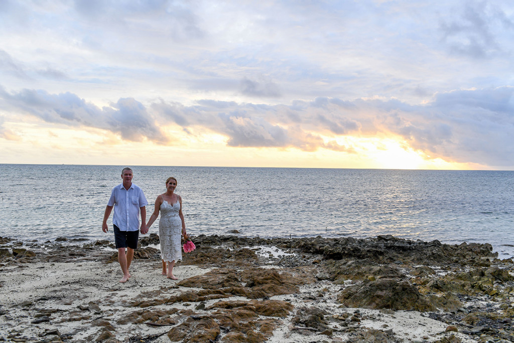 Newly married couple walk on coral rocks in Fiji Plantation Island Resort