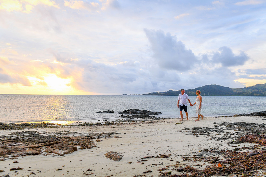 Bride and groom stroll on the beach in fiery Fiji wedding