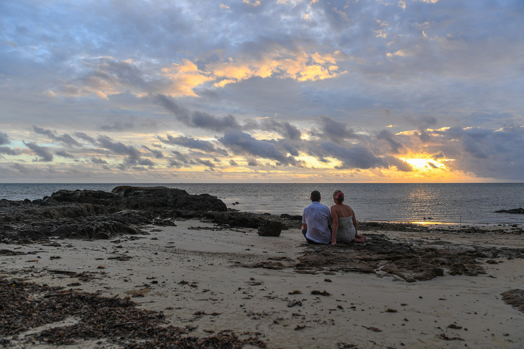 Bride and groom sit and watch the sunset in Fiji Island Resort Wedding