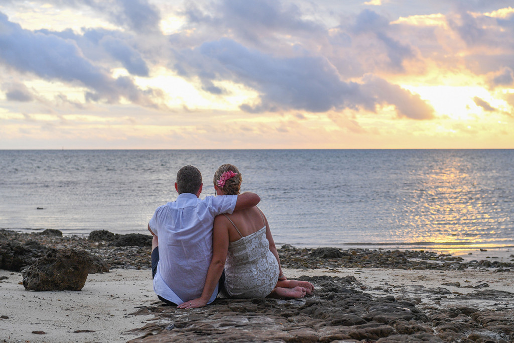 Bride and groom sit and watch sunset over the sea in Fiji Island