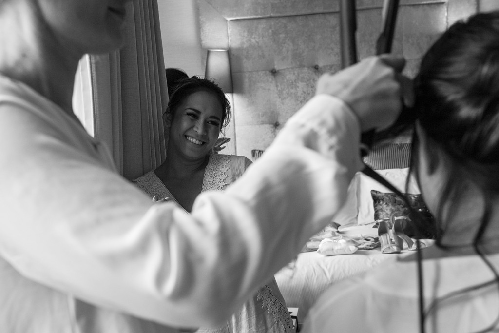 Black and white photo of bridesmaid smiling during wedding preparations