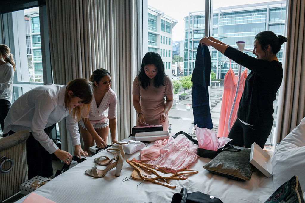Bridesmaids sorting out their dresses during wedding preparations