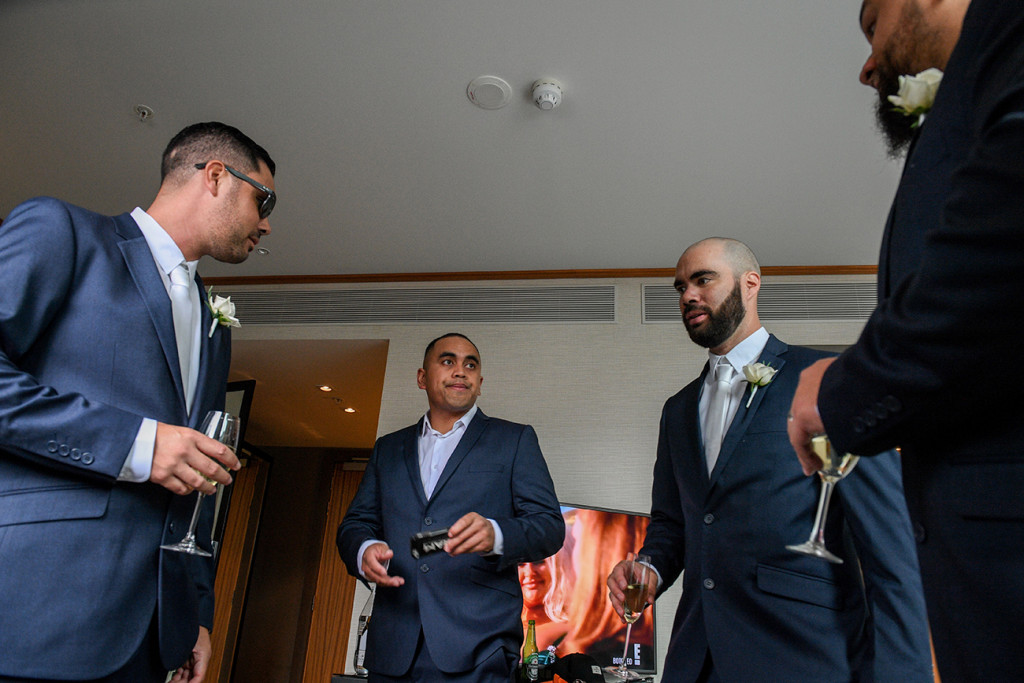 Groomsmen drink champagne as they wait for the cermony