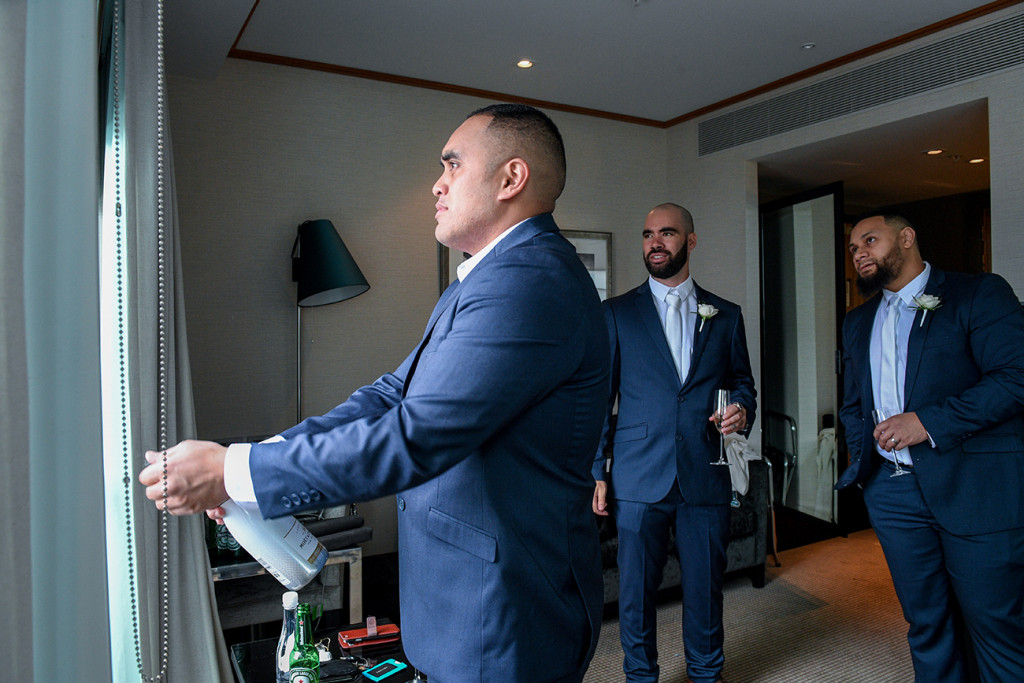 Groom pops champagne bottle open during wedding preparation in Auckland Sofitel